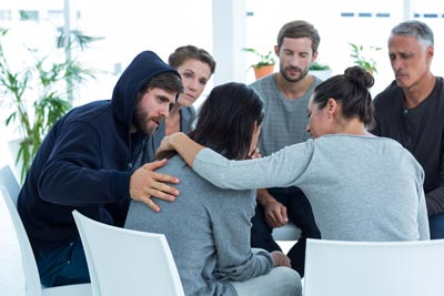 People sitting in circle comforting lady